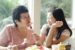 """""""mother and daughter happily eating together"""