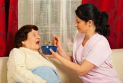 caregiver giving food to the senior woman