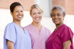 nurses standing outside a hospital while smiling